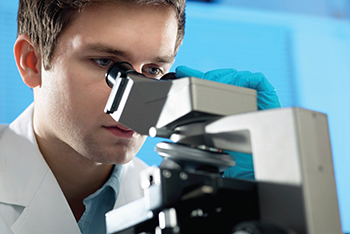 researcher peering into a microscope